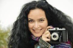 Jeune femme de brune avec l'appareil-photo de fhoto sur le film prenant des photos Photo stock