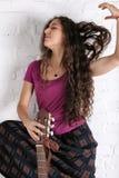 Jeune femme de brune avec la guitare acoustique dans la longue jupe Fond de mur de briques Image libre de droits