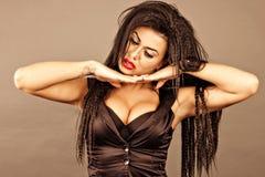 Jeune femme de brune avec le maquillage créatif tenant sa tête sur l'ha Images libres de droits
