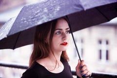 Jeune femme de brune avec le parapluie sous la pluie photo libre de droits