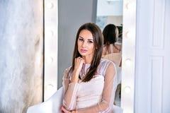 Jeune femme de brune avec les cheveux droits et soyeux se reposant devant le miroir sur le fond gris Photographie stock