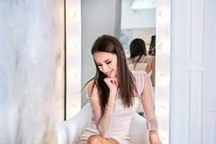 Jeune femme de brune avec les cheveux droits et soyeux se reposant devant le miroir sur le fond gris et regardant vers le bas Photos stock