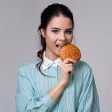 Jeune femme de brune avec un bisquit Photographie stock libre de droits