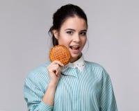 Jeune femme de brune avec un bisquit Photos stock