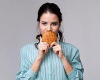 Jeune femme de brune avec un bisquit Images libres de droits