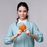 Jeune femme de brune avec un bisquit Photos libres de droits