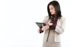 Jeune femme de brune avec un PC de comprimé d'isolement sur le blanc Photographie stock libre de droits