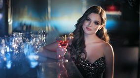 Jeune femme de brune de beauté s'asseyant à la barre avec le verre de vin dans l'intérieur de luxe banque de vidéos