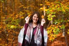 Jeune femme de brune dans des feuilles de participation de forêt photo stock