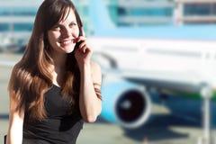 Jeune femme de brune dans l'aéroport Photographie stock libre de droits