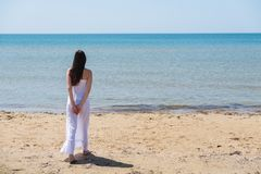 Jeune femme de brune dans la robe blanche d'été se tenant sur la plage et regardant à la mer images stock