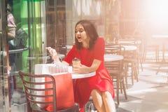 jeune femme de brune dans la robe rouge regardant dans des sacs à provisions dans un café après l'achat le mail image stock