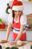 Jeune femme de brune faisant cuire la pizza ou les pâtes faites main tout en utilisant le chapeau de Santa Claus dans la cuisine  Images libres de droits