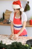 Jeune femme de brune faisant cuire la pizza ou les pâtes faites main tout en utilisant le chapeau de Santa Claus dans la cuisine  Image stock