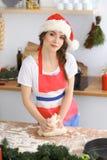 Jeune femme de brune faisant cuire la pizza ou les pâtes faites main tout en utilisant le chapeau de Santa Claus dans la cuisine  Images stock