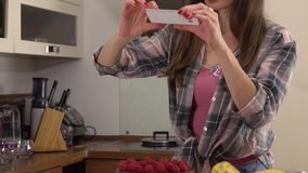 Jeune femme de brune faisant des photos de son gâteau de chocolat et de framboise Vidéo de Steadicam 4K clips vidéos