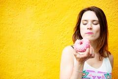 Jeune femme de brune mangeant un beignet photo stock
