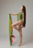 Jeune femme de brune marchant avec de longs cheveux et planche de surf Images libres de droits