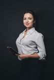 Jeune femme de brune posant contre le noir Photos stock