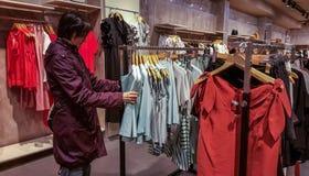 Jeune femme de brune regardant une robe à la mode dans une boutique d'habillement à Eskisehir Images libres de droits