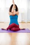 Jeune femme de brune s'asseyant en position de yoga et méditant photographie stock