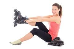 Jeune femme de brune s'asseyant et mettant sur des patins Image stock