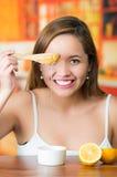 Jeune femme de brune s'asseyant tenant le couteau en bois avec l'égoutture d'or de miel de elle, souriant heureusement Photographie stock libre de droits