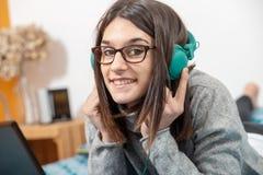 Jeune femme de brune se trouvant sur le lit écoutant la musique images stock