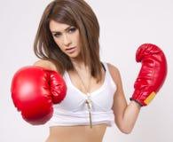 Jeune femme de brunette avec les gants de boxe rouges Image stock