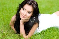 Jeune femme de brunette sur l'herbe verte Photographie stock