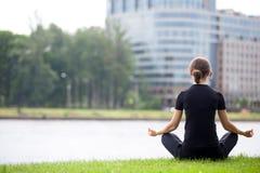 Jeune femme de bureau s'asseyant dans la pose de yoga Image stock