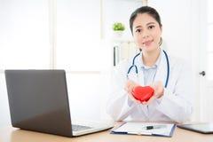 Jeune femme de cardiologue employant le service en ligne Photographie stock libre de droits