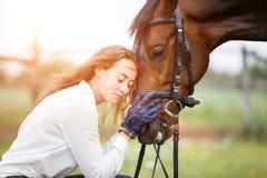 Jeune femme de cavalier dans la chemise se penchant à la tête de cheval Photos stock