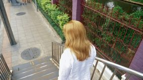 Jeune femme de charme avec les cheveux d'or, marchant au centre de la ville, elle marche à travers le pont banque de vidéos