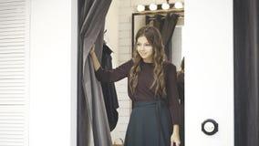 Jeune femme de cheveux onduleux dans une cabine d'essayage de boutique image libre de droits