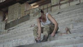 Jeune femme de Confidient dans l'uniforme militaire se reposant sur les escaliers concrets froids dans le bâtiment abandonné, laç clips vidéos