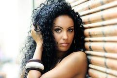 Jeune femme de couleur à l'arrière-plan urbain Photo stock