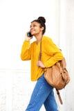 Jeune femme de couleur attirante parlant au téléphone portable Photo stock
