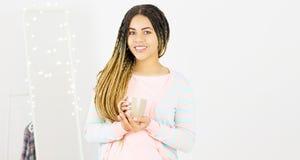 Jeune femme de couleur avec le sourire Afro de coiffure Fille avec la boisson chaude de tasse portant la robe rose Projectile de  photographie stock libre de droits