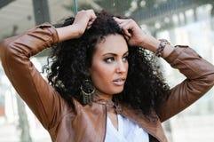 Jeune femme de couleur, coiffure Afro, à l'arrière-plan urbain Photos libres de droits