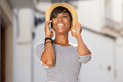 Jeune femme de couleur gaie parlant au téléphone portable images libres de droits