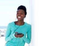 Jeune femme de couleur heureuse avec le téléphone et les écouteurs intelligents photographie stock libre de droits