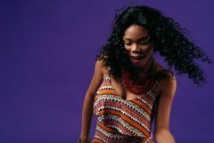 Jeune femme de couleur heureuse et danse sur un fond lilas Photos libres de droits