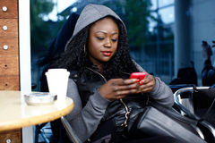 Jeune femme de couleur occupée avec le téléphone portable Images libres de droits