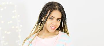 Jeune femme de couleur de portrait avec les cheveux Afro Fond gris photographie stock