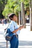 Jeune femme de couleur de portrait latéral marchant dehors avec le téléphone portable photographie stock