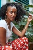 Jeune femme de couleur s'asseyant dehors et touchant ses cheveux image stock