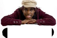 Jeune femme de couleur se penchant au-dessus d'un signe blanc pour l'espace de copie Photos libres de droits