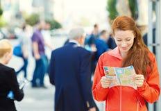 Jeune femme de déplacement lisant une carte photos stock