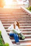 Jeune femme de déplacement s'asseyant avec la carte sur des escaliers Photo libre de droits